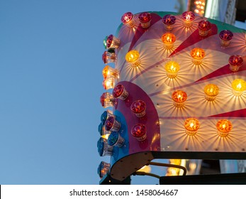 Colorful Carnival lights against blue evening sky. Landscape orientation.