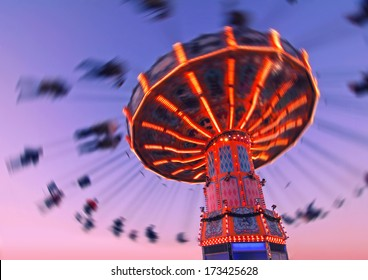 colorful carousel in motion with sundown in background, people enjoy their ride in the carousel