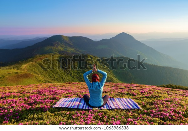 Colorful carpet. The yoga girl in the lotus pose. The lawn with the rhododendron flowers. High mountains. Magical forest. Meditation. Relax. Summer scenery. Warm morning sun rays.