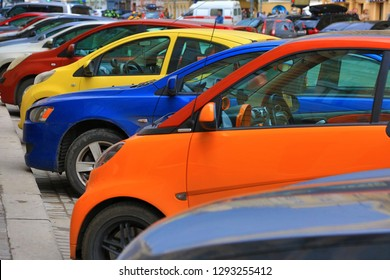 Colorful cars parked on the street. Yellow blue red orange silver and black automobiles.