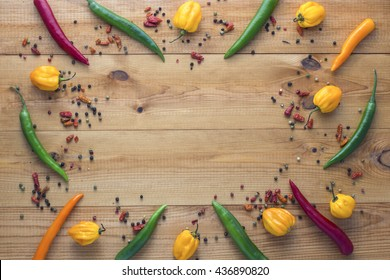 Colorful cayenne chilli peppers, yellow habanero peppers, pepperoncini peppers and color pepper on wooden table with copyspace in the centre. Top view.