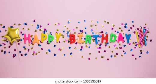 Colorful celebration background with various party confetti and candle decoration. Minimal birthday concept. Flat lay.