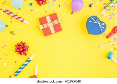 Colorful celebration pattern with various party confetti, balloons, gift box on yellow background. Flat lay