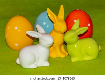 Colorful ceramic easter eggs and Easter bunnies in front of a green background.