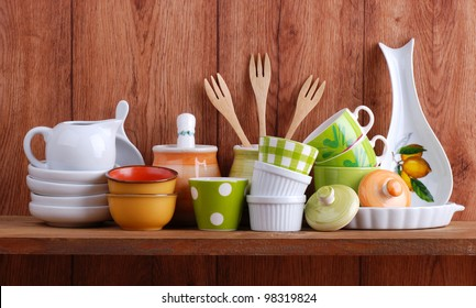 colorful ceramic kitchen utensils on wooden shelf
