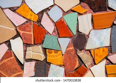 Colorful ceramic mosaic floor. Creative recycled mosaic top view photo. Bathroom or kitchen floor design idea. Red orange ceramic piece. Reused broken tile. Interior design. Colored eastern pottery