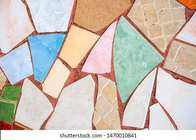 Colorful ceramic mosaic floor. Creative recycled mosaic top view photo. Bathroom or kitchen floor design idea. Blue yellow ceramic tiles. Reused broken tile. Outdoor paving. Colored eastern pottery