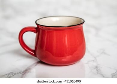 Colorful ceramic mug with enamel look on white marble background
