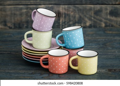 Colorful ceramic mugs with enamel look on blue wooden background