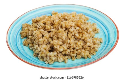 Colorful ceramic plate with cooked pearl barley porridge. Isolated over white background