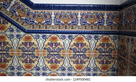 Colorful ceramic tiled wall finish entrance hall stairs well in village in Andalusia