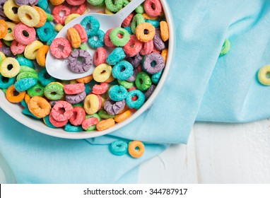 Colorful cereal in white bowl with shoon on a white background