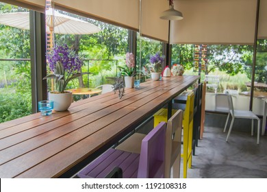 Colorful chairs in the glass room with blind, curtain, roller, shade, shutter protected sunlight, outside is a green garden that Select focus point.
