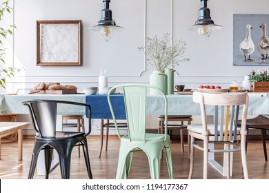 Colorful chairs at table in eclectic grey dining room interior with lamps and flowers. Real photo