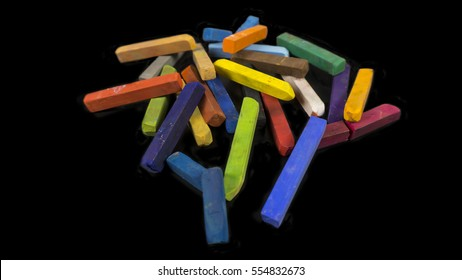 Colorful chalk pastels pile up on a black background