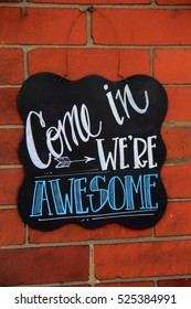 Colorful chalkboard sign, attached to old brick wall, invites visitors to come in and visit
