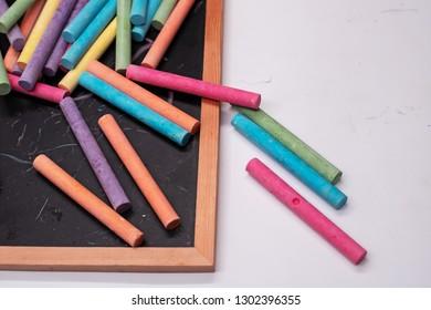 The colorful chalks put on blackboard