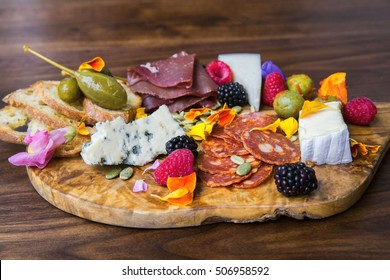 Colorful charcuterie board of meat, cheese, berries, edible flowers, olives, and pickles on a wooden cutting board