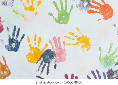 Colorful children hand prints on white wall background,palms and fingers paint