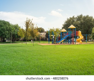 Colorful children playground activities in public park surrounded by green trees at sunset in Houston, Texas. Children run, slide, swing on modern playground. Urban neighborhood childhood concept.