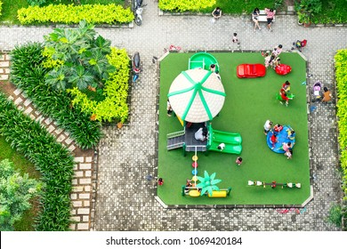 Colorful children playground on yard activities in public park surrounded by green trees at sunlight morning. Children run, slide, swing on modern playground. Urban neighborhood childhood concept.