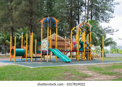 Colorful children playground in public park surrounded by green trees
