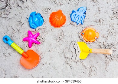 Colorful Children's beach toys on sand, top view