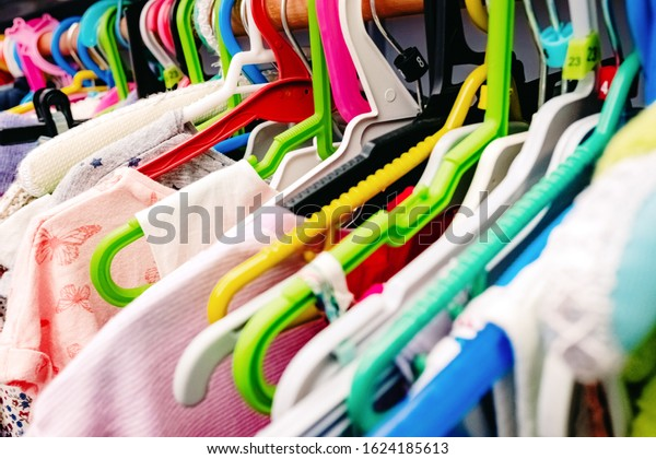 Colorful children's dresses hanging on hangers in a closet.