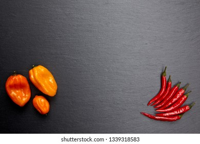 Colorful chili peppers on dark stone plate