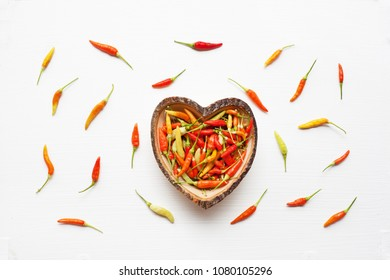 Colorful chili peppers in wooden dish heart shape on white.