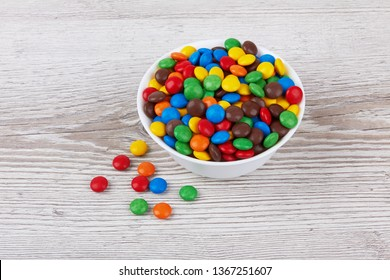 colorful chocolate buttons on wooden background