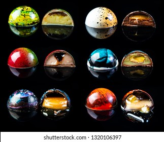 Colorful chocolate candy in a cut on the black glossy background with reflection