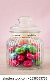 Colorful chocolate candy jar decorated with bow ribbon against pink background, gifts for Easter