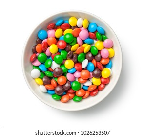 Colorful chocolate candy pills in bowl isolated on white background. Top view