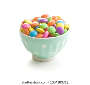 Colorful chocolate candy pills in bowl isolated on white background.