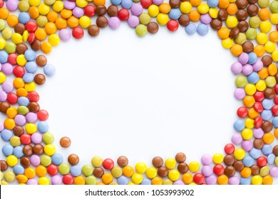 A lot of colorful chocolate candy top view, blank space to put text. White background.