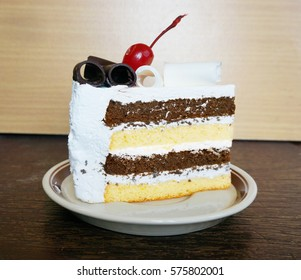 Colorful chocolate - vanilla layer cake decorated with cherry and chocolate topping on wooden background, close up