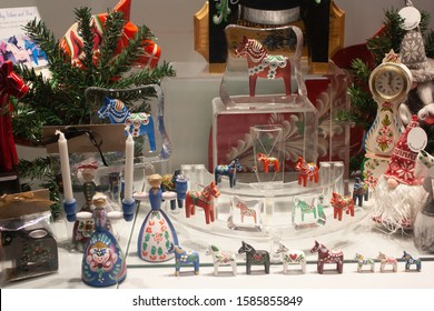 Colorful Christmas decoration with wooden horses, dwarfs, dolls, candles, Christmas tree branch and decorative clock.