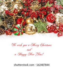 Colorful christmas decorations in red, gold, green. Festive background with falling snow effect. Sample text Merry Christmas