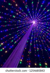 """Colorful Christmas lights strung from a flagpole creates a lighted Christmas tree effect, seen in this view looking up from inside the """"tree""""."""