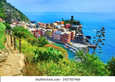 Colorful Cinque Terre village of Vernazza, Italy. Above view with hiking trail and blue sea.