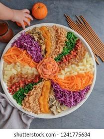Colorful and circular arrangement of chinese festive cuisine / Carousel of Prosperity Toss / Radish, carrot, mandarin orange, jelly fish, pineapple, smoked salmon, baby octopus, deep fried fish skin