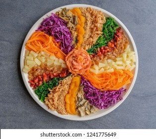 Colorful and circular arrangement of chinese festive cuisine / Carousel of Prosperity Toss / Radish, carrot, mandarin orange, jelly fish, pineapple, smoked salmon, baby octopus, deep fried fish skin