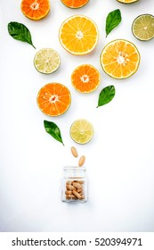 Colorful of citrus fruits, cut orange, lime,lemon, with vitamin c tablet in glass bottle on white background.In concept of vitamin C.Extract vitamin c from fruits. Supplementary health food nutrition.