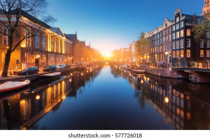 Colorful cityscape at sunset in Amsterdam, Netherlands. Reflected city lights in water with blue sky at twilight. Night illumination of buildings and boats on the water. Travel. Beautiful street