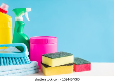 Colorful cleaning set for different surfaces in kitchen, bathroom and other rooms. Empty place for text or logo on blue background. Cleaning service concept. Early spring regular clean up. Front view.