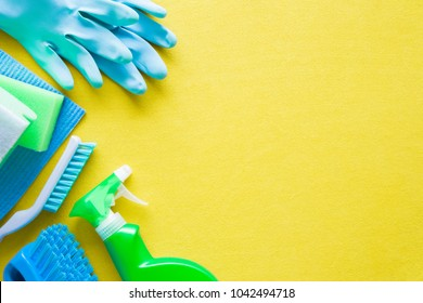 Colorful cleaning set for different surfaces in kitchen, bathroom and other rooms. Empty place for text or logo on yellow background. Cleaning service concept. Early spring regular clean up. Top view.