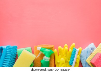 Colorful cleaning set for different surfaces in kitchen, bathroom and other rooms. Empty place for text or logo on pink background. Cleaning service concept. Early spring regular clean up. Top view.