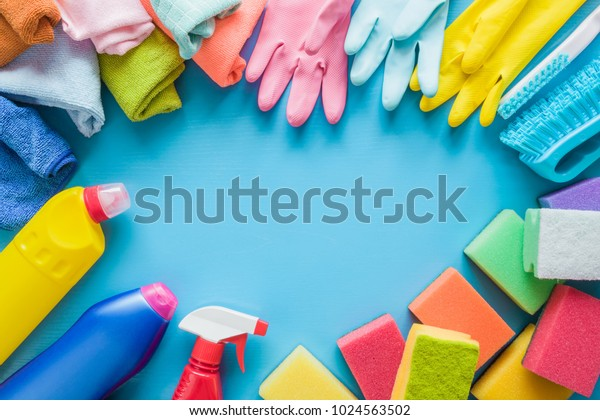Colorful cleaning set for different surfaces in kitchen, bathroom and other rooms. Empty place for text or logo on blue background. Cleaning service concept. Early spring regular clean up. Top view.