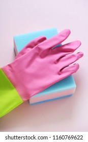 colorful cleaning utensils (rubber glove and sponge) on pink background